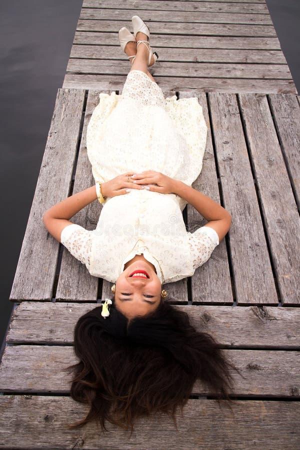 Ragazza asiatica in un vestito bianco che si trova su un bacino fotografia stock libera da diritti