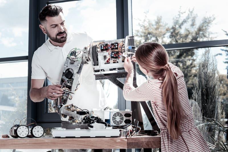 Ragazza astuta che aiuta il suo insegnante con la macchina robot fotografia stock