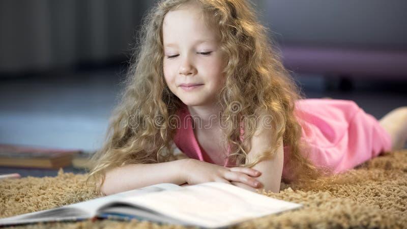 Ragazza astuta che legge libro interessante, letteratura per i bambini, istruzione immagine stock libera da diritti
