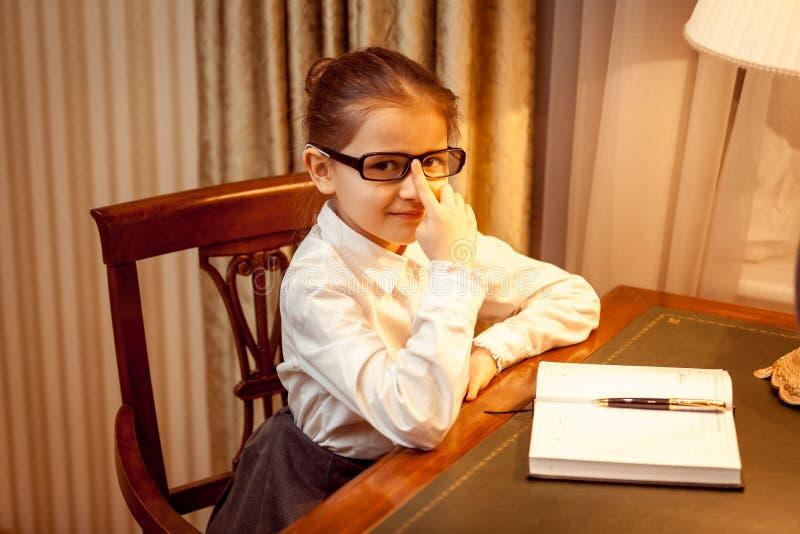 Ragazza astuta che si siede dietro la tavola con il taccuino immagini stock libere da diritti