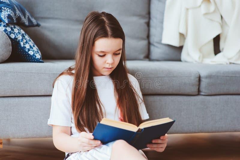 ragazza astuta del bambino che legge libro interessante fotografia stock