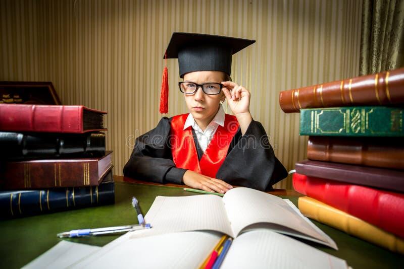 Ragazza astuta nella graduazione in abito accademico che esamina macchina fotografica fotografia stock libera da diritti