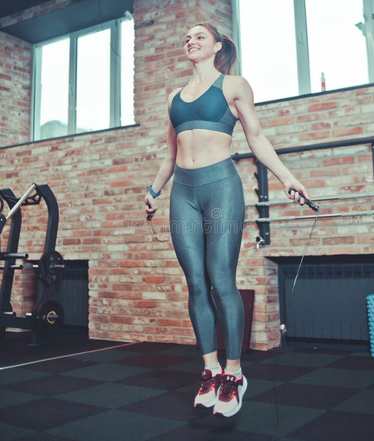 Ragazza atletica allegra nell'addestramento della donna degli abiti sportivi con un salto della corda immagine stock libera da diritti
