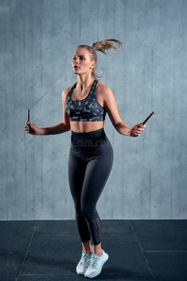 Ragazza atletica allegra nell'addestramento della donna degli abiti sportivi con un salto della corda in una palestra su una pare fotografie stock