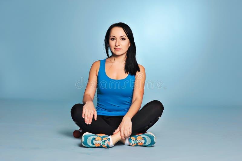 Ragazza atletica con il corpo del muscolo che si siede sul pavimento fotografia stock libera da diritti