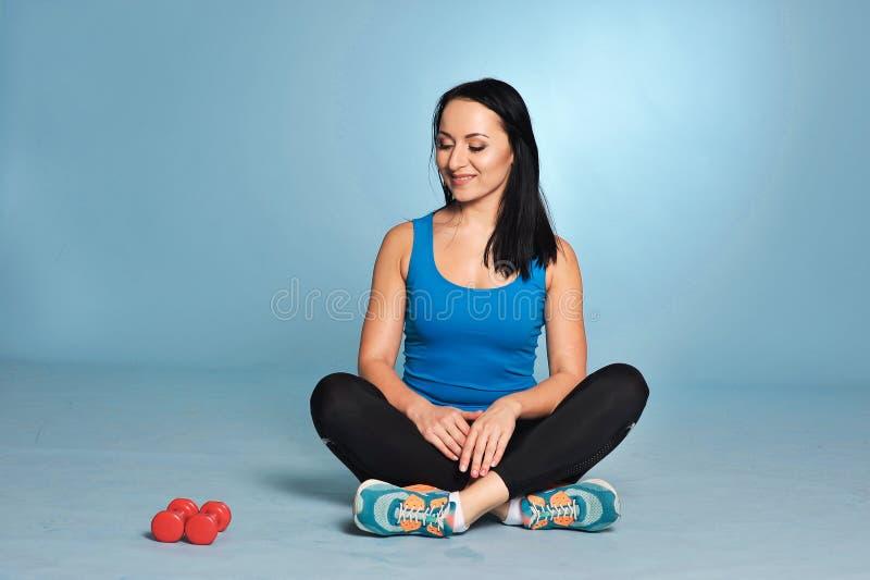 Ragazza atletica con il corpo del muscolo che si siede sul pavimento fotografia stock
