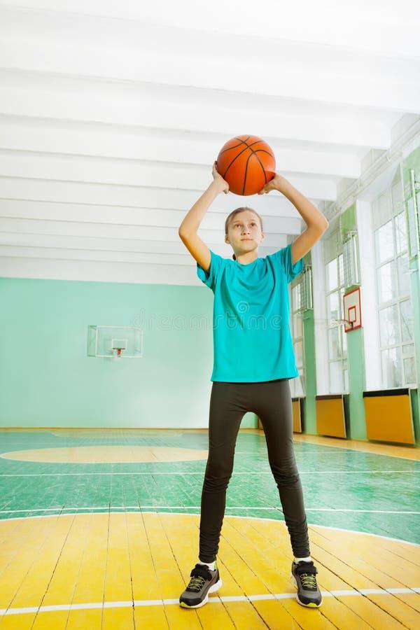 Ragazza attiva del preteen che lancia pallacanestro in orlo fotografie stock