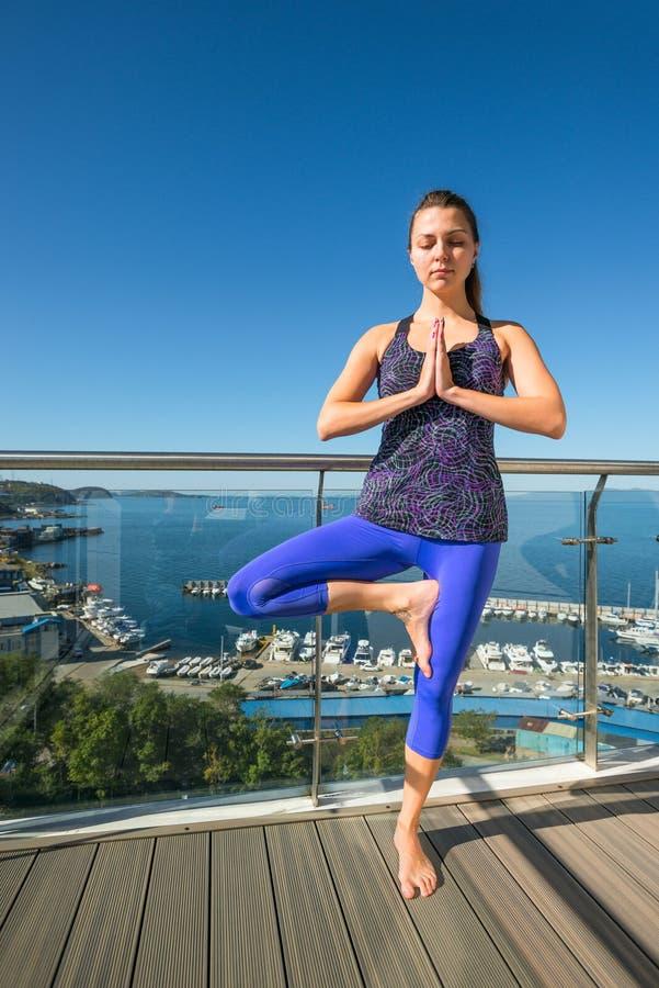 Ragazza attiva in una posa dell'albero su un terrazzo aperto sui precedenti del mare Il concetto di uno stile di vita sano yoga fotografie stock