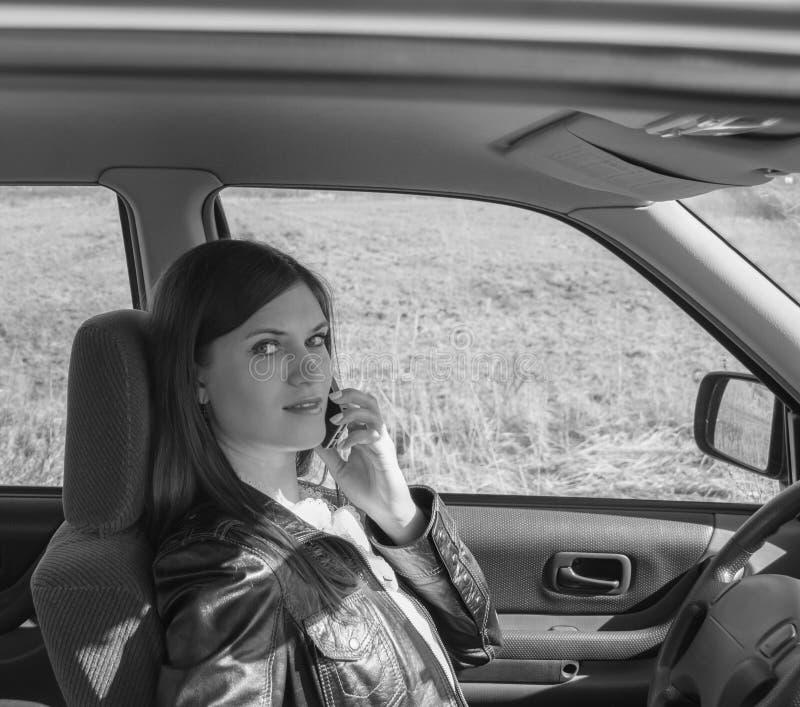 Ragazza attraente in bianco e nero nell'automobile che parla sul telefono fotografia stock libera da diritti