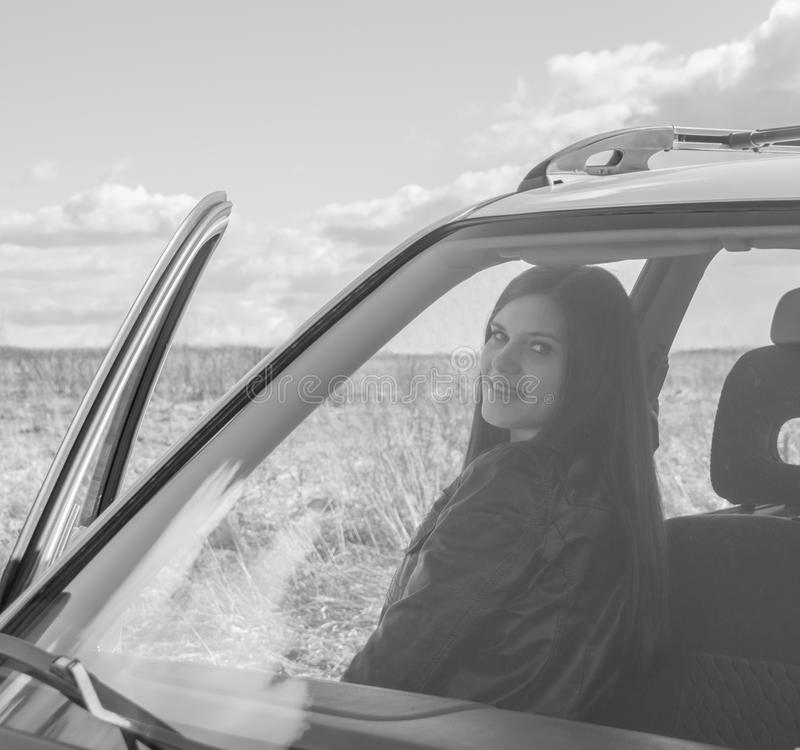 Ragazza attraente in bianco e nero nell'automobile con la porta aperta fotografia stock libera da diritti