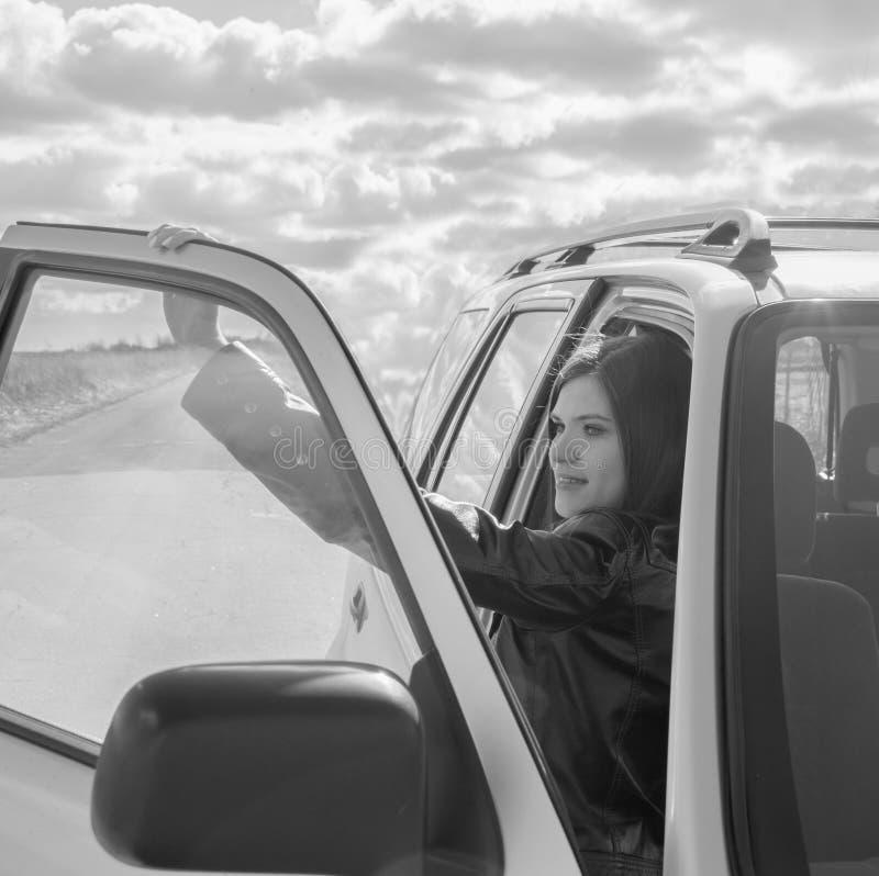 ragazza attraente in bianco e nero nell'automobile nel sedile del passeggero fotografia stock