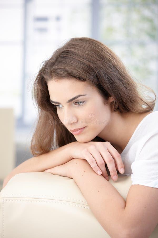 Ragazza attraente che daydreaming sul sofà nel paese immagini stock libere da diritti