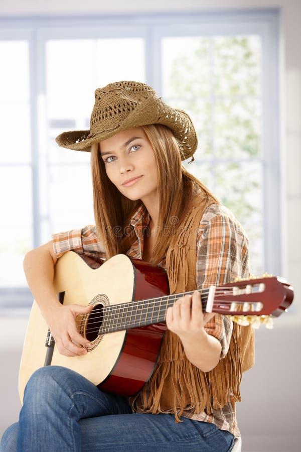 Ragazza attraente che gioca chitarra in cappello occidentale fotografia stock