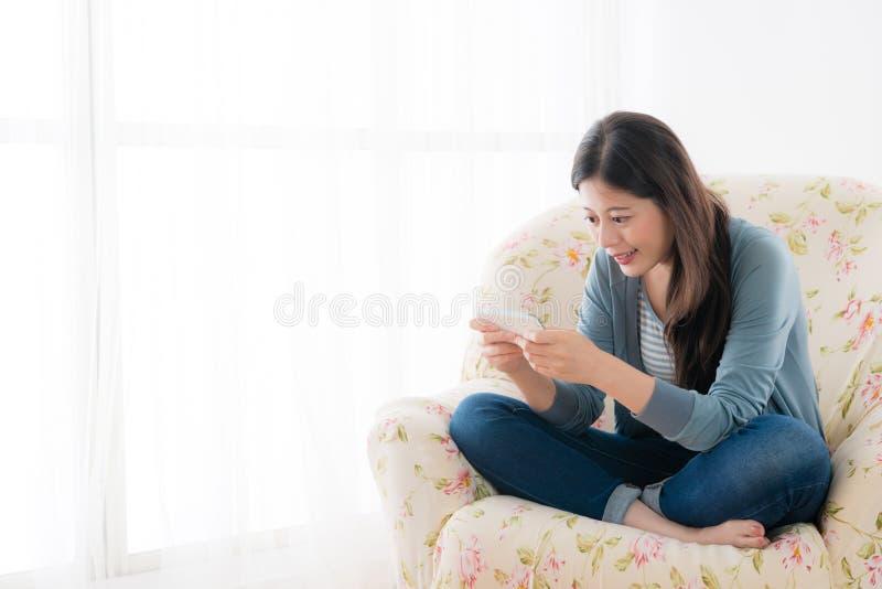 Ragazza attraente che per mezzo del telefono che gioca gioco online fotografie stock