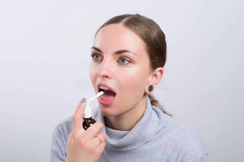 Ragazza attraente che prende una medicina con spruzzo dentro la gola su fondo leggero fotografia stock libera da diritti