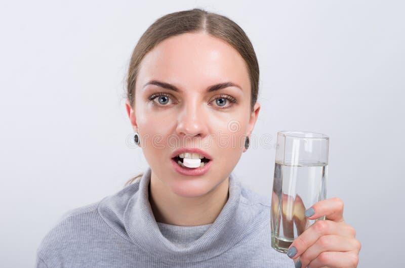 Ragazza attraente che prende una pillola con acqua su fondo leggero immagini stock