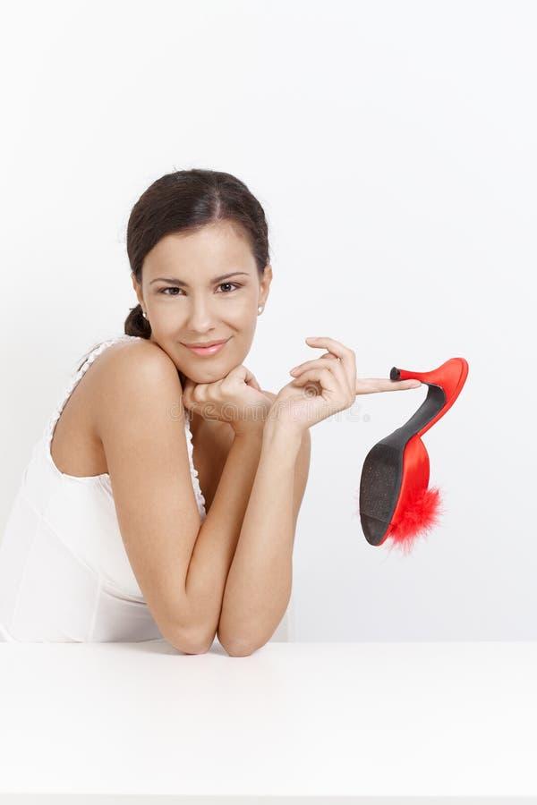 Ragazza attraente che propone con i pistoni di colore rosso dell'alto tallone fotografie stock