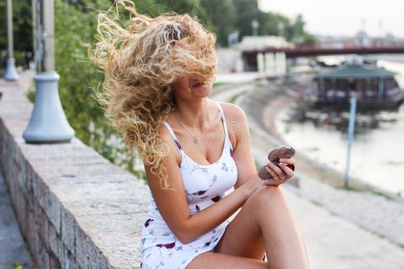 Ragazza attraente con capelli biondi ricci che provano a riparare la sua m. fotografie stock