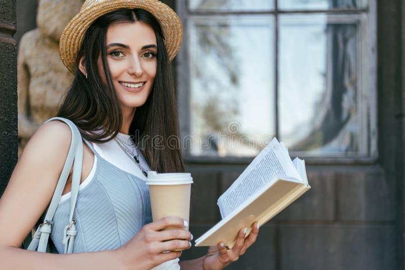 ragazza attraente con il libro e sorridere di lettura della tazza di carta immagine stock libera da diritti
