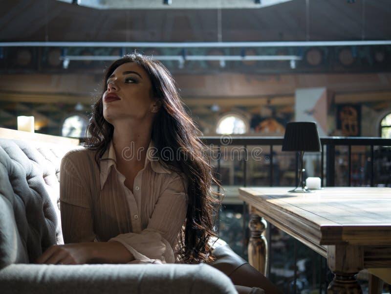 Ragazza attraente con le pose splendide dei capelli per la macchina fotografica mentre sedendosi sul sofà all'interno immagini stock libere da diritti