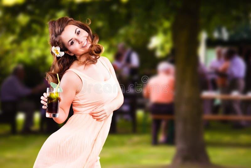 Ragazza attraente con una bevanda davanti ad un fondo di estate fotografia stock