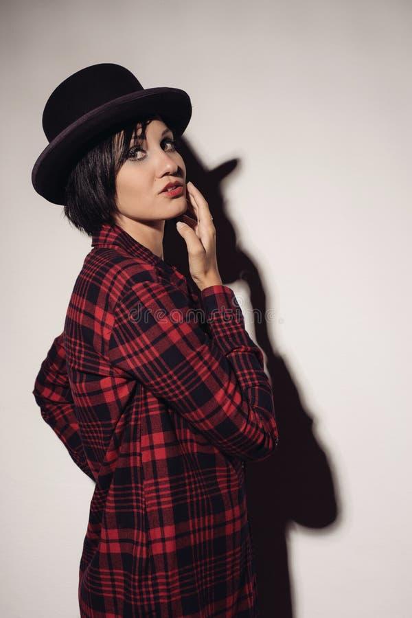 Ragazza attraente in giocatore di bocce a quadretti rosso del cappello e della camicia fotografia stock