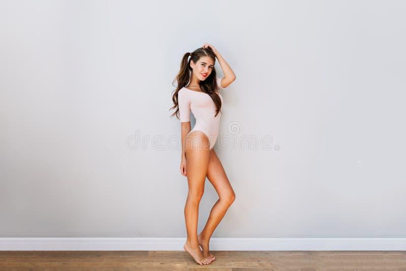 Ragazza attraente graziosa in tuta rosa in appartamento moderno Giovane donna allegra con capelli castana lunghi che sorride con  immagini stock libere da diritti