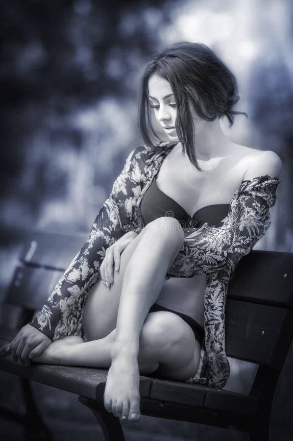 Ragazza attraente nella seduta del costume da bagno rilassata su un banco Modello femminile alla moda con il sembrare romantico c immagine stock libera da diritti