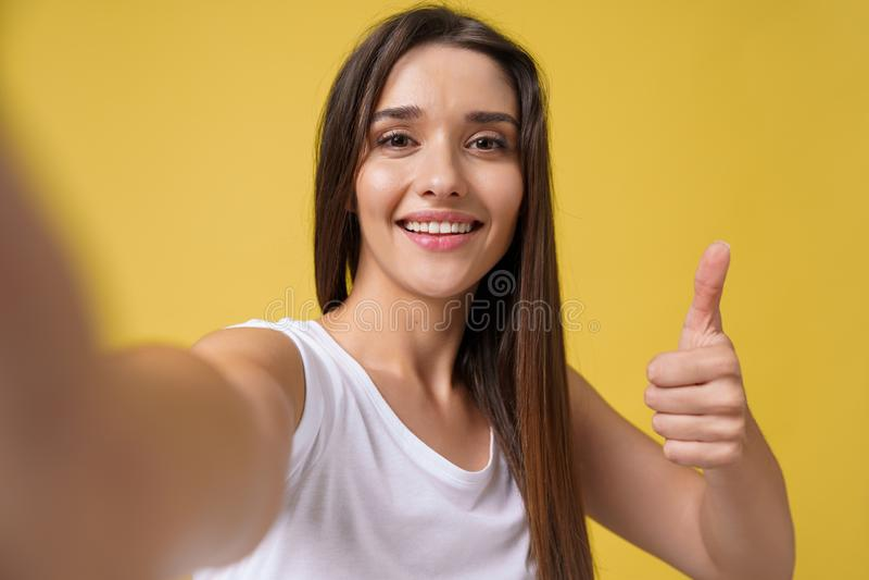 Ragazza attraente piacevole che fa selfie in studio e nella risata Bella giovane donna con capelli marroni che prendono immagine fotografia stock libera da diritti