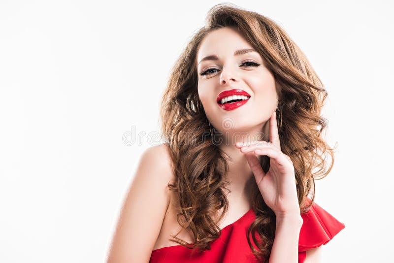 ragazza attraente sorridente con trucco e le labbra rosse che toccano fronte con la mano fotografia stock