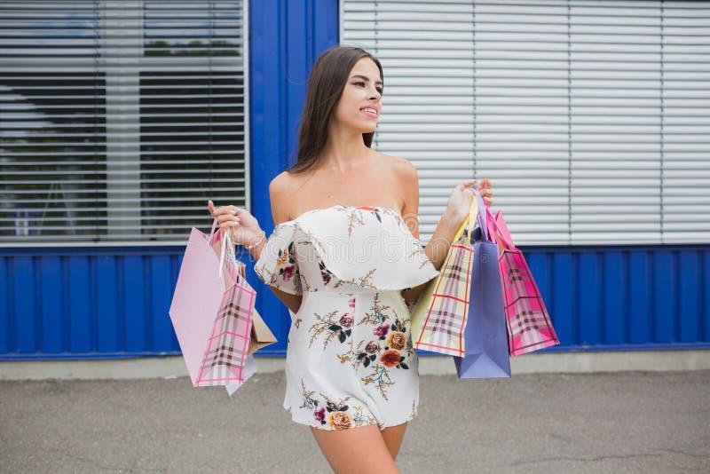 Ragazza attraente, sveglia e sorridente dentro con i sacchetti della spesa variopinti in sue mani Esaminare la distanza fotografia stock libera da diritti