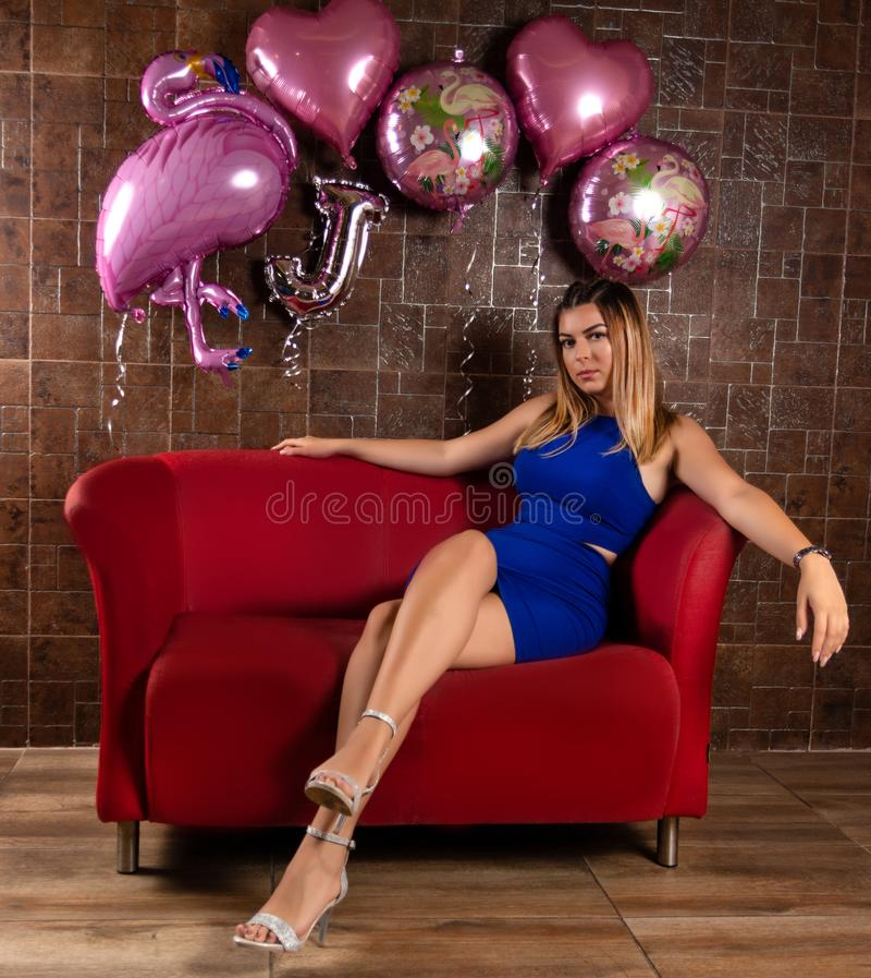 Ragazza attraente in un breve vestito elegante blu che si siede in una sedia ed in una posa rosse fotografia stock