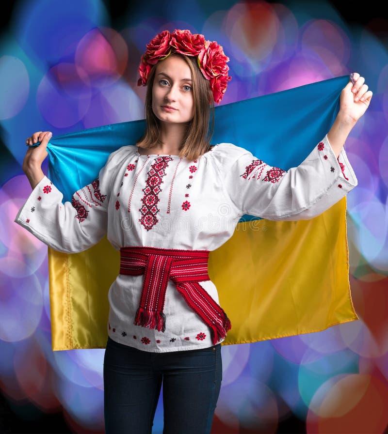 Ragazza attraente in vestito nazionale con la bandiera ucraina immagini stock
