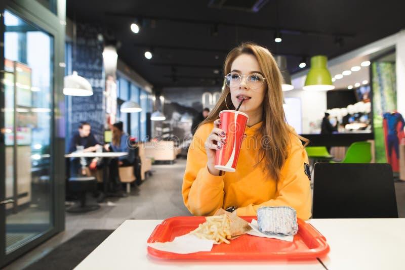 Ragazza attraente in vetri che si siedono nel fast food con un vassoio di patate fritte e di hamburger e di cola della bevanda fotografie stock libere da diritti