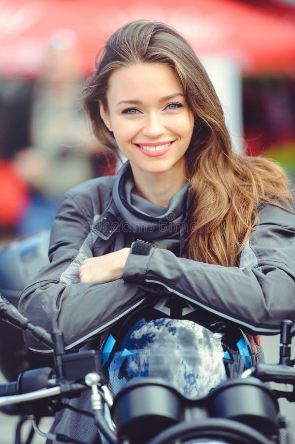 Ragazza in attrezzatura di moto con un motociclo immagini stock libere da diritti