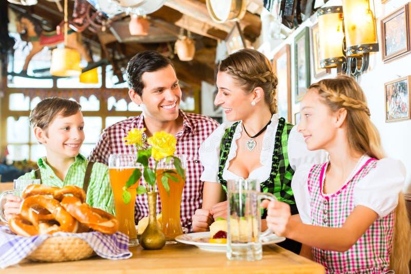 Ragazza bavarese con la famiglia in ristorante fotografia stock
