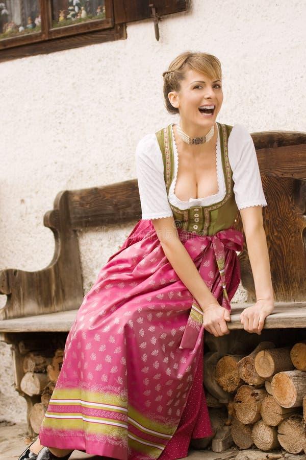Ragazza bavarese in vestito tradizionale ad una banca immagini stock libere da diritti