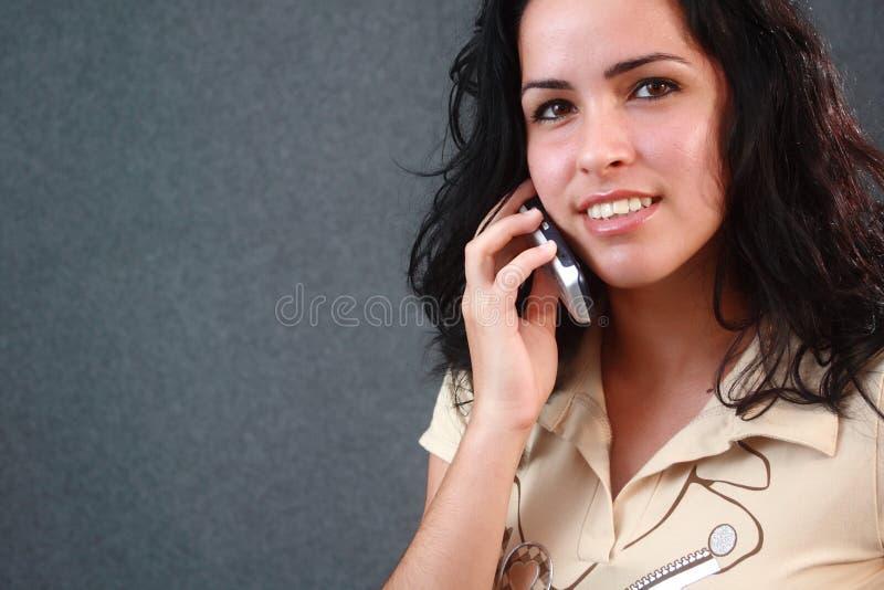 Ragazza bella che comunica su un telefono delle cellule immagini stock