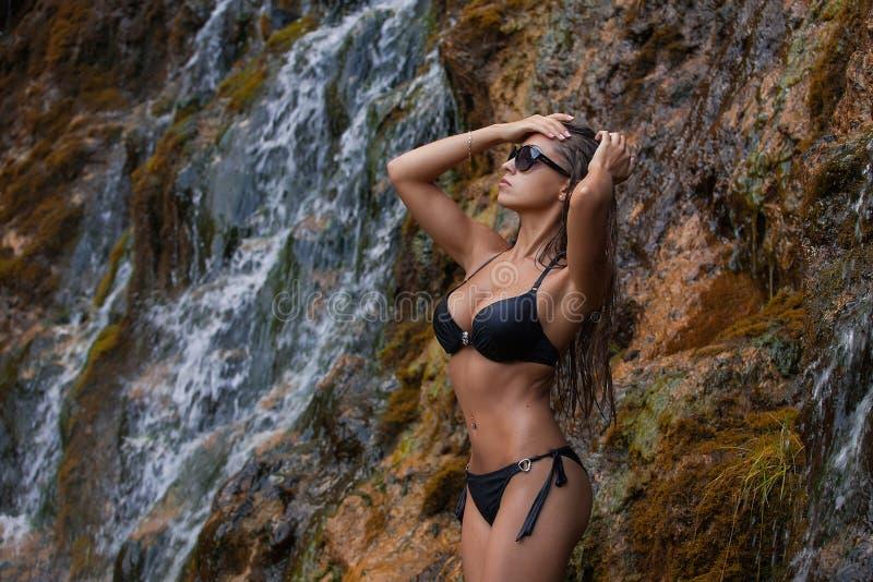 Ragazza bella in costume da bagno che sta al piede della cascata fotografia stock libera da diritti