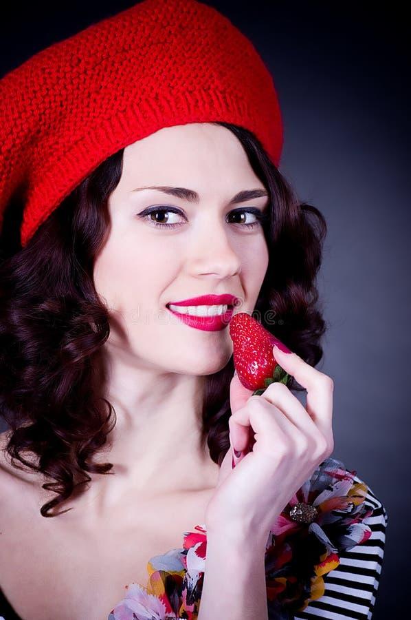Ragazza in berreto rosso che mangia fragola. fotografia stock