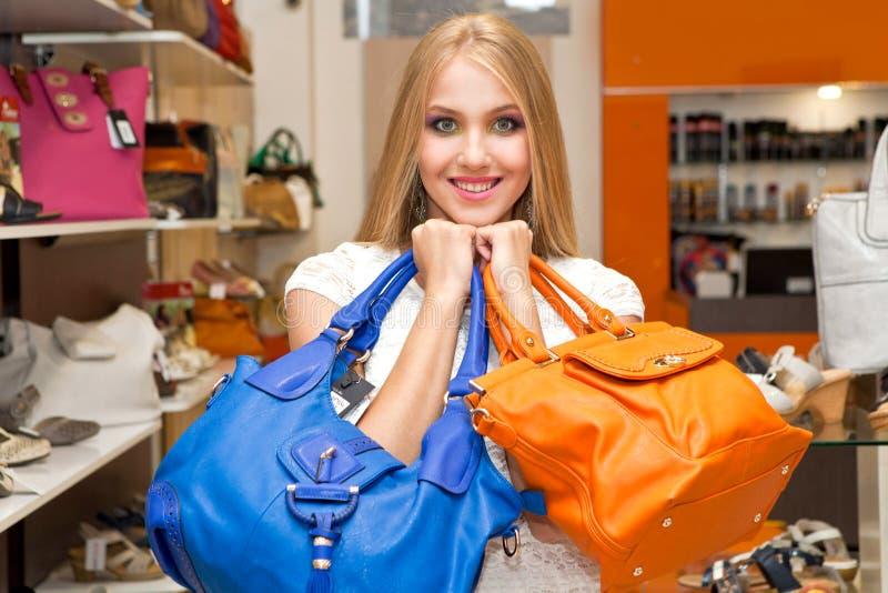 Ragazza bianca con le borse di cuoio in loro mani nel deposito delle borse Ragazza e borse immagini stock libere da diritti