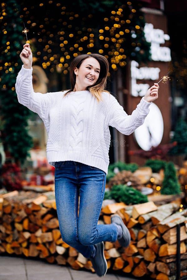 Ragazza bianca felice con capelli scuri lunghi in maglione, ghirlande nel bokeh, atmosfera accogliente di festa, donna sorridente immagini stock libere da diritti