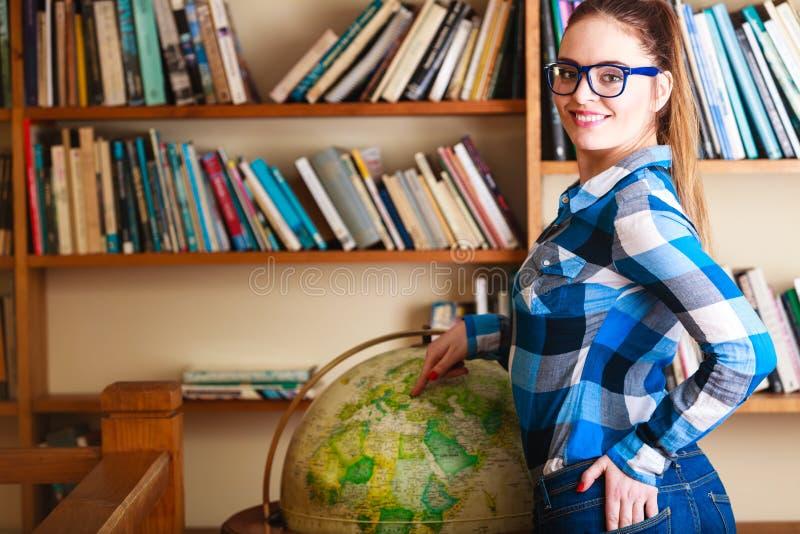 Ragazza in biblioteca che indica il globo immagine stock