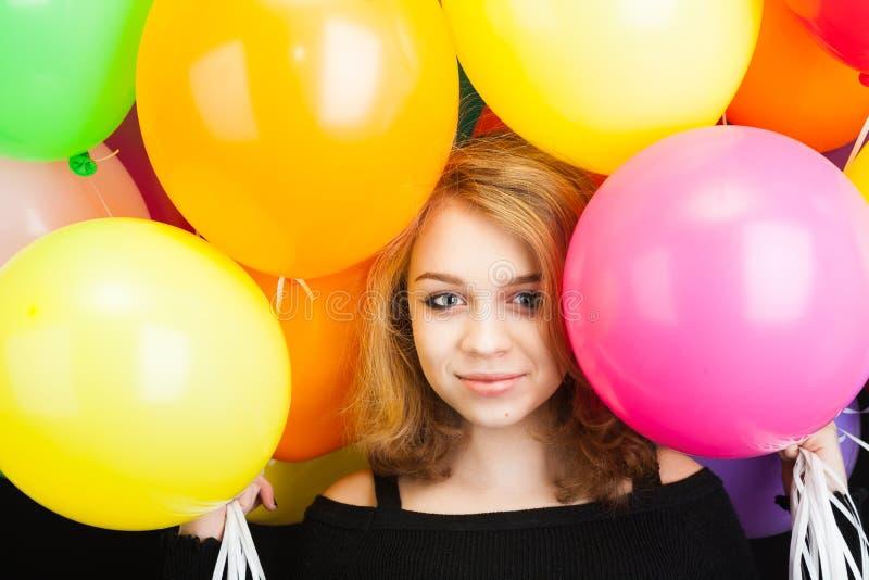Ragazza bionda adolescente sorridente con i palloni variopinti fotografia stock