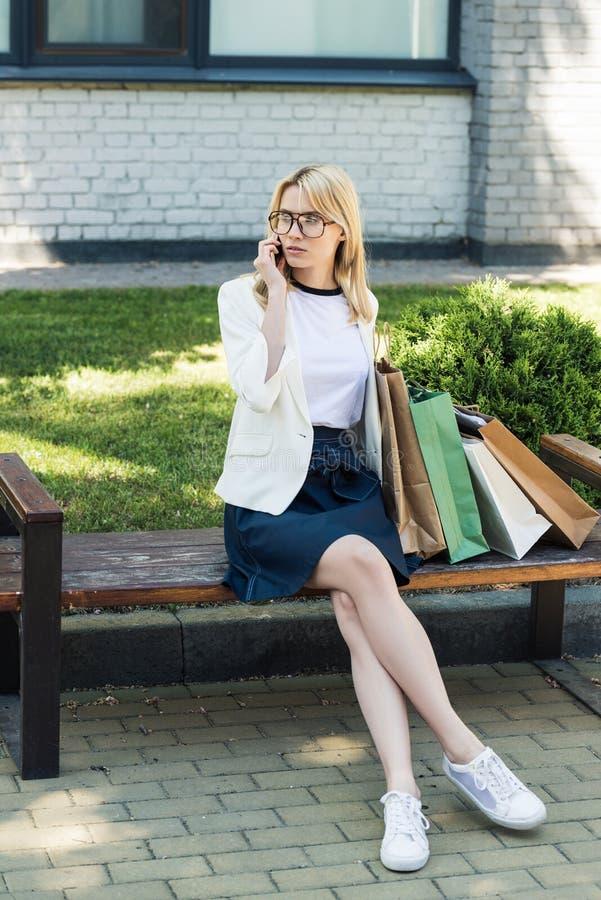 ragazza bionda alla moda con i sacchetti della spesa che si siedono sul banco e sulla conversazione immagini stock