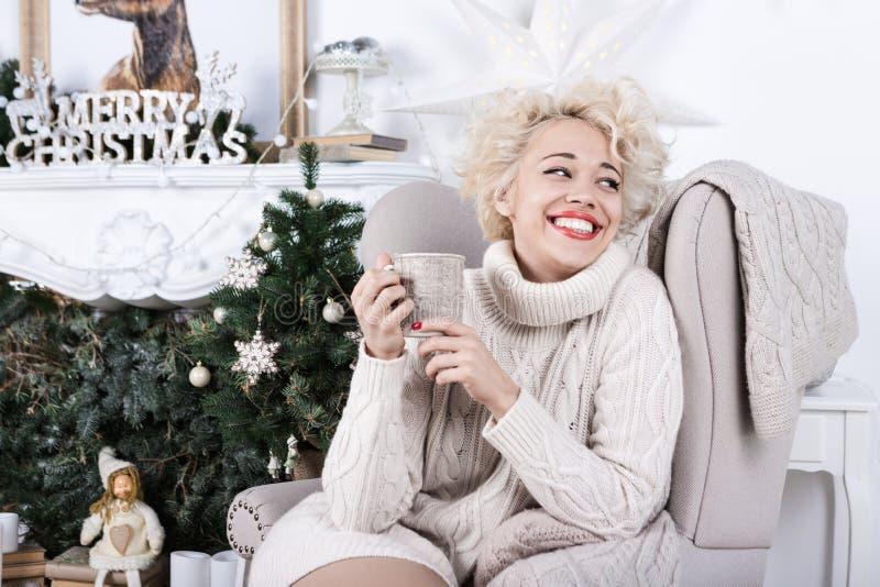 Ragazza bionda attraente che si siede in una sedia fotografia stock libera da diritti