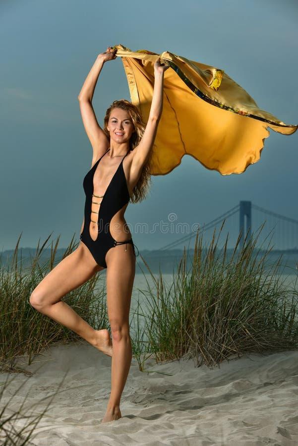 Ragazza bionda attraente con l'ente esile di misura che posa sulla spiaggia che porta costume da bagno nero elegante fotografie stock