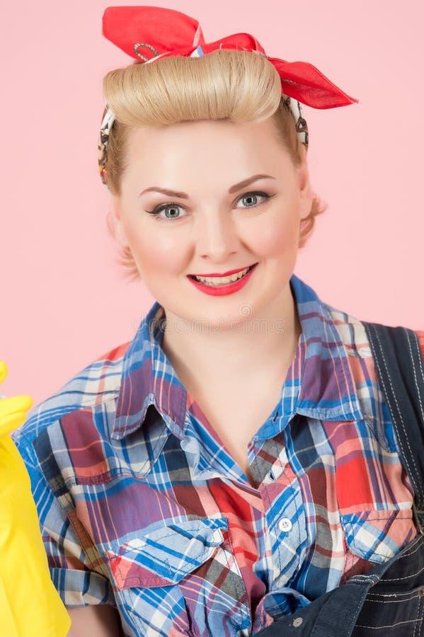 Ragazza bionda attraente con trucco di pin-up Bello sorriso della donna bionda con la sciarpa rossa sulla testa sul fondo di rosa immagini stock