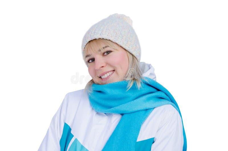 Ragazza bionda attraente in rivestimento di sport, cappello e sciarpa blu con il sorriso che esamina la macchina fotografica Isol fotografia stock libera da diritti