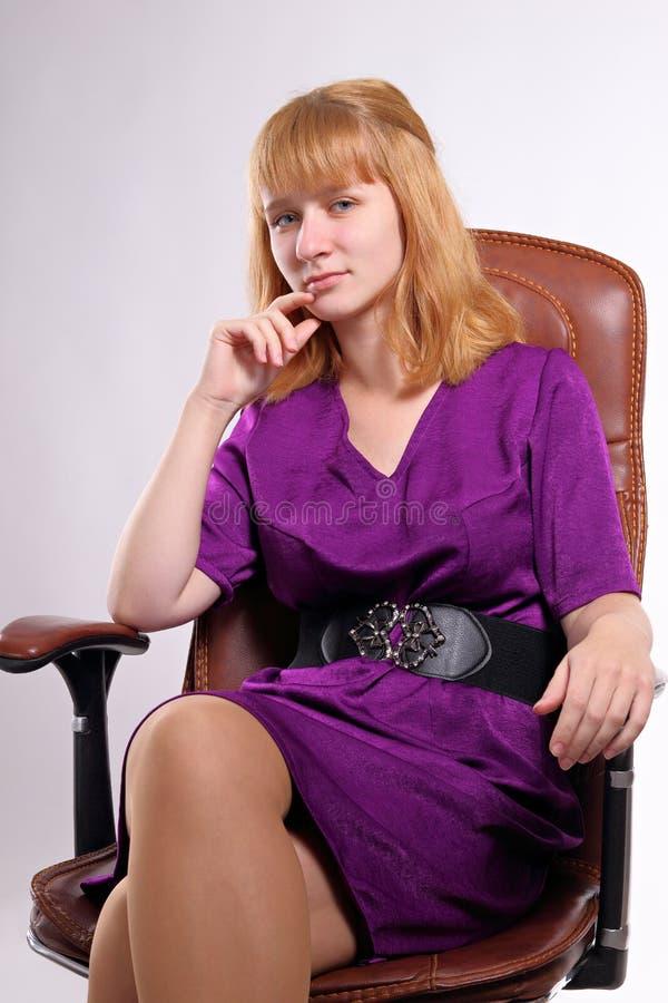 Ragazza bionda caucasica che si siede in una sedia dell'ufficio immagini stock